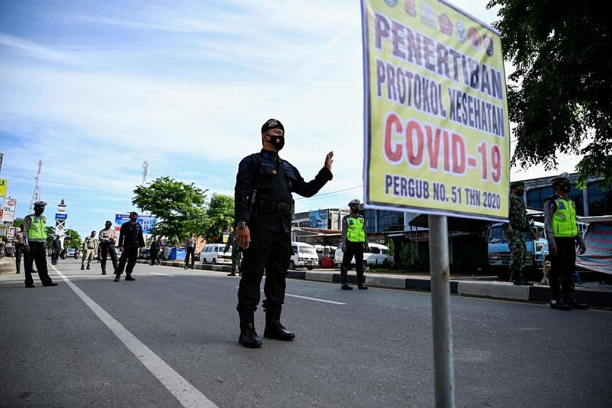 Law enforcement officers stop and check motorists during lockdown restrictions at a checkpoint in Lambaro, Aceh province, on July 16, 2021.