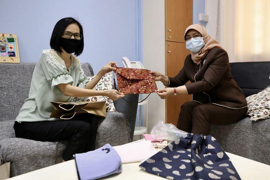 Madam Fan Bee Eng presenting President Halimah Yacob with a handsewn bag at Fei Yue Family Service Centre (Choa Chu Kang).