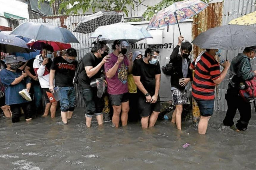 Thousands waded through ankle-to knee-high floodwaters to get into San Andres Sports Complex.