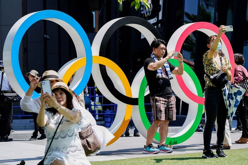 People take selfies in front of an Olympic Rings monument near the National Stadium, in Tokyo.