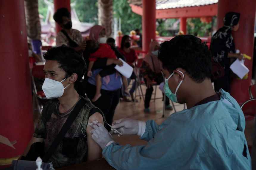 A health worker administers a dose of the Sinovac Biotech Ltd. Covid-19 vaccine at a vaccination center in Semarang, Central Java, Indonesia, on Wednesday, July 21, 2021.