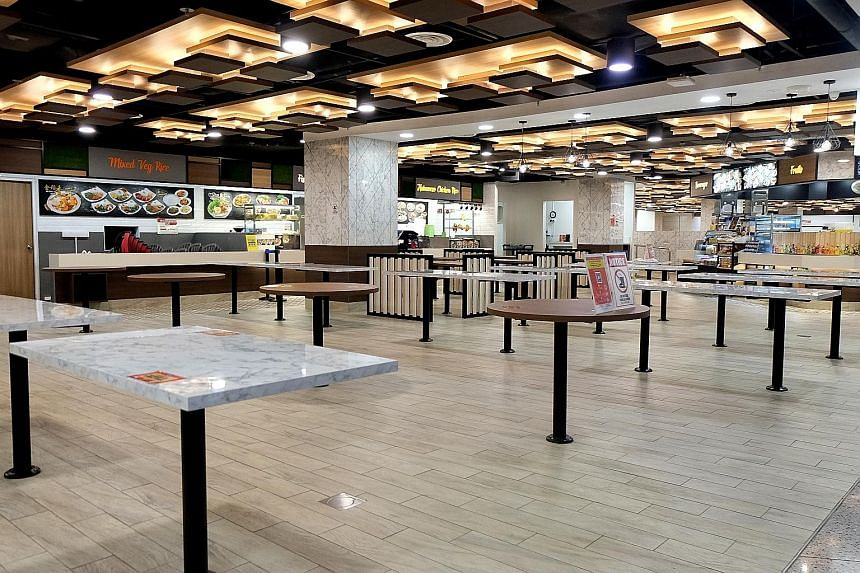 An empty Koufu Foodcourt at Orchard Cineleisure around 5.30pm yesterday, which marked the start of restrictions on dining in. Patrons can only take away purchased food. A stall selling pork was among the few stalls open at Geylang Bahru Market and Fo