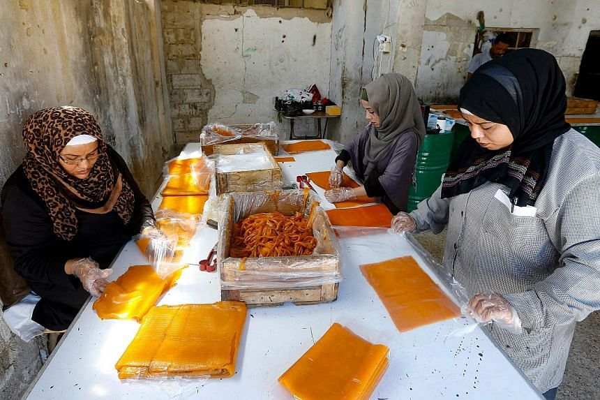 Apricot juice is mixed with sugar, then cooked and spread onto wooden boards (right) to be left to dry in the sun (above) in the Eastern Ghouta region on the outskirts of the Syrian capital Damascus. It is part of the process to make the popular Qama