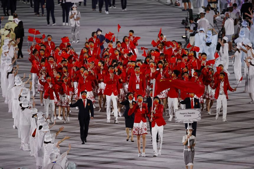 Zhao Shuai of China and Ting Zhu of China lead their contingent in the athletes' parade.