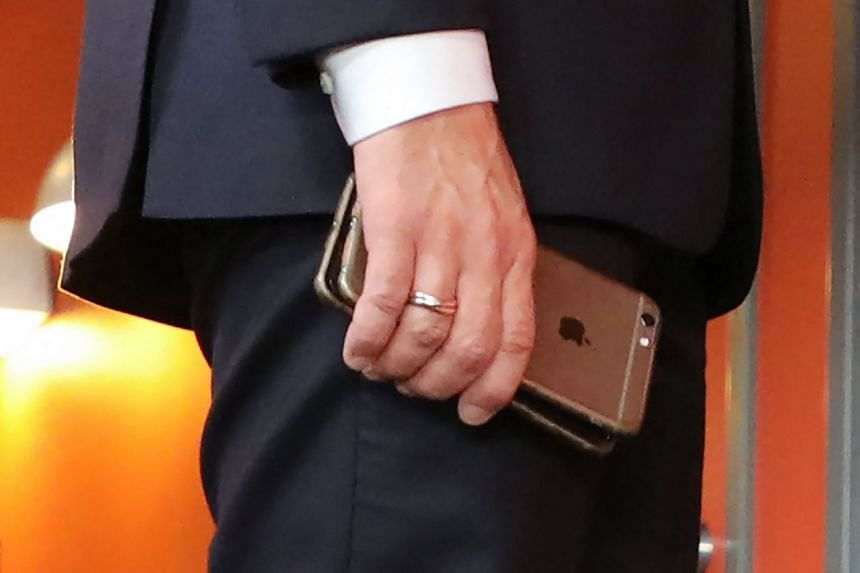 A 2017 photo shows French President Emmanuel Macron holding his mobile phone during a summit in Sweden.