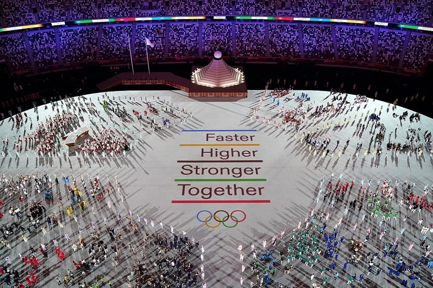 Above: Athletes gathering around the new motto last night in the stadium. Left: One of the performances during the ceremony.