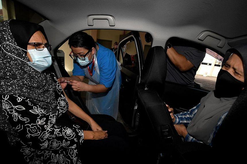 Madam Sabarina Othman, 67, receiving her Covid-19 vaccine shot at a drive-through vaccination centre at Universiti Sains Malaysia in Penang. PHOTO: BERNAMA