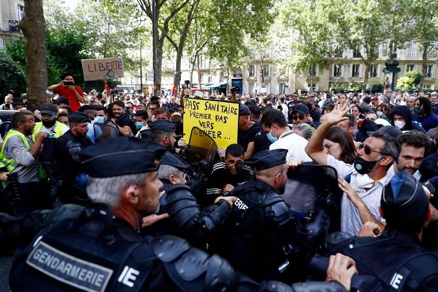 French riot police face protesters, some wearing yellow vests, during an anti-Covid measures demonstration in Paris on July 24, 2021.