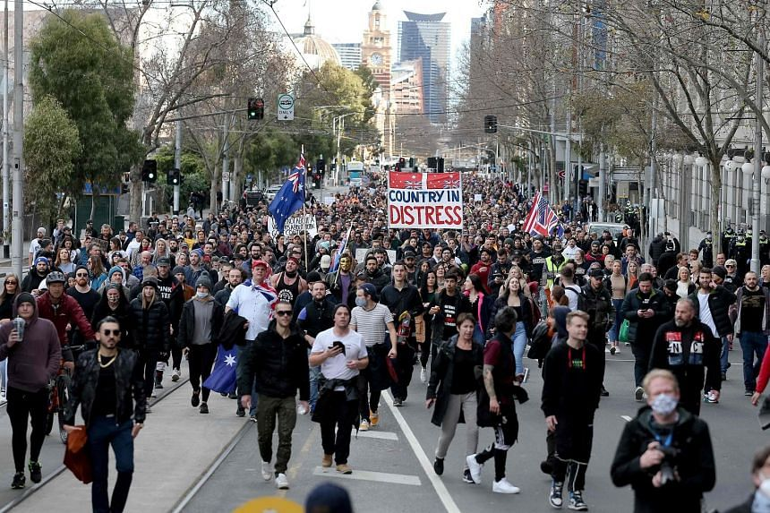 Protesters taking part in a rally in Melbourne yesterday. The largely maskless protesters were flouting rules on non-essential travel and public gatherings, a day after the authorities suggested the restrictions could remain in place until October. P