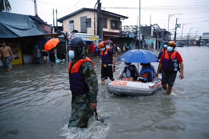Rescuers pull a rubber boat along a flooded road in Las Pinas city, Metro Manila, Philippines, on July 24, 2021.