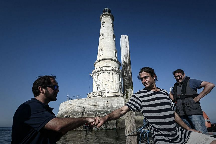 Lighthouse keeper Thomas Dalisson (centre), 38, bids farewell to his colleague Nicolas Quezel-Guerraz, 43, as he leaves the Cordouan lighthouse in June 2021.