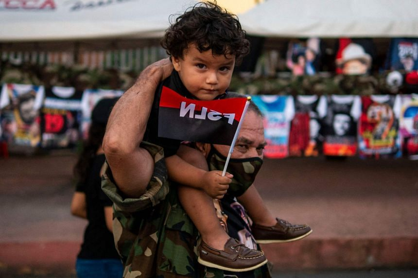 A supporter of Nicaraguan President Daniel Ortega carries a child on his shoulders holding a Sandinista National Liberation Front flag in Managua on July 19, 2021.