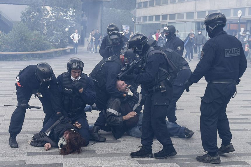 French police officers detain two protestors during a demonstration in Nantes, western France, on July 24, 2021.