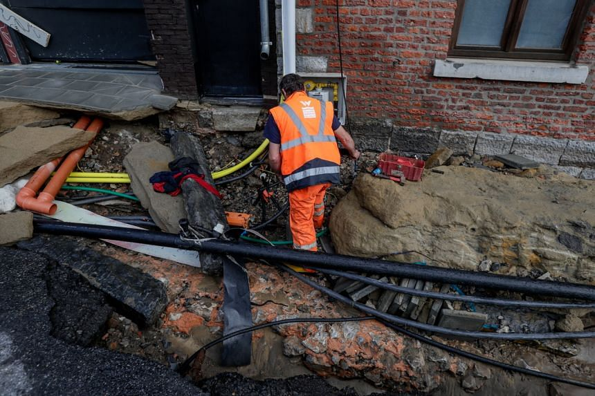 A municipal worker repairs the pipes of a damaged street in Dinant, Belgium, on July 24, 2021.