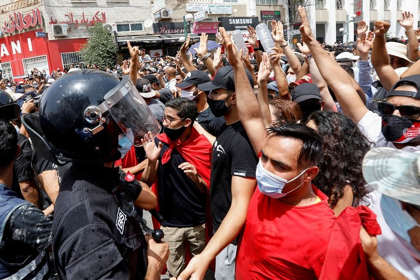 Demonstrators gather in front of police officers standing guard during an anti-government protest in Tunis, Tunisia on July 25, 2021.