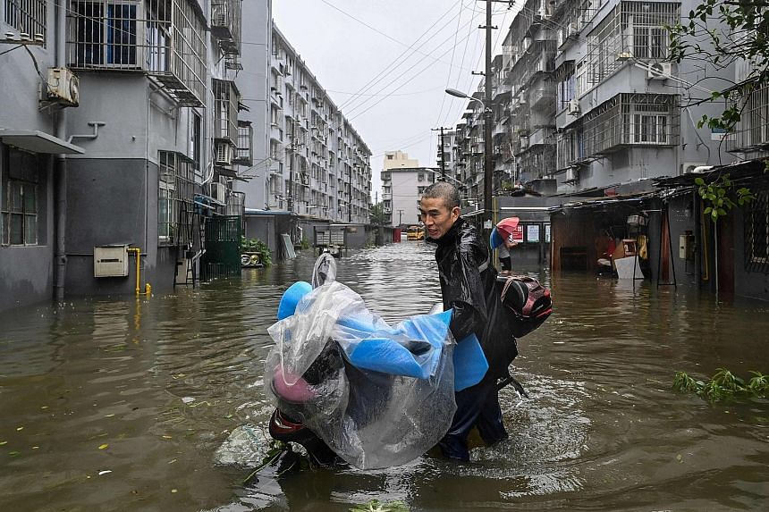 A man pushing a scooter in a flooded street in Ningbo, Zhejiang province, yesterday as Typhoon In-fa lashed the eastern coast of China.