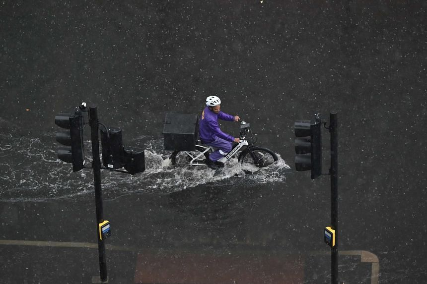 A cyclist rides through water on a flooded road in The Nine Elms district of London on July 25, 2021.