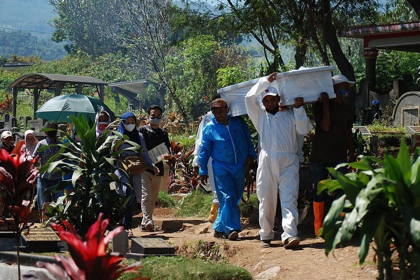 Gravediggers carry the coffin of a man who died of Covid-19 as they head towards a cemetery in Bandung on July 25, 2021.