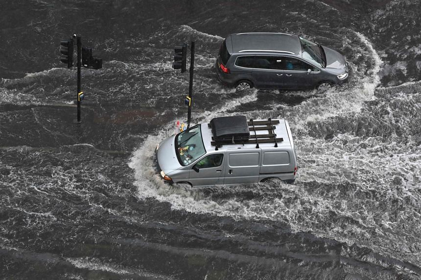 Vehicles drive through deep water on a flooded road in The Nine Elms district of London on July 25, 2021.