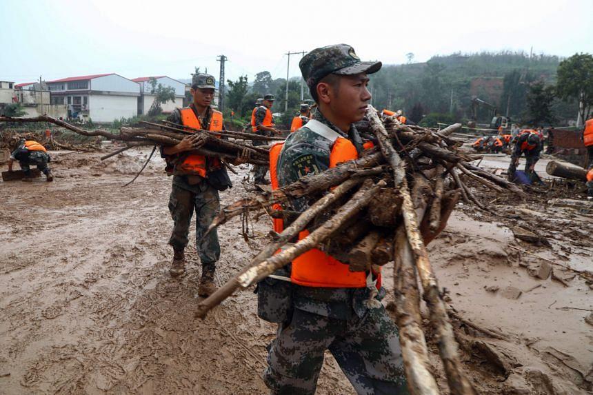 Soldiers clean up a street following floods in Zhengzhou, Henan, on July 24, 2021.