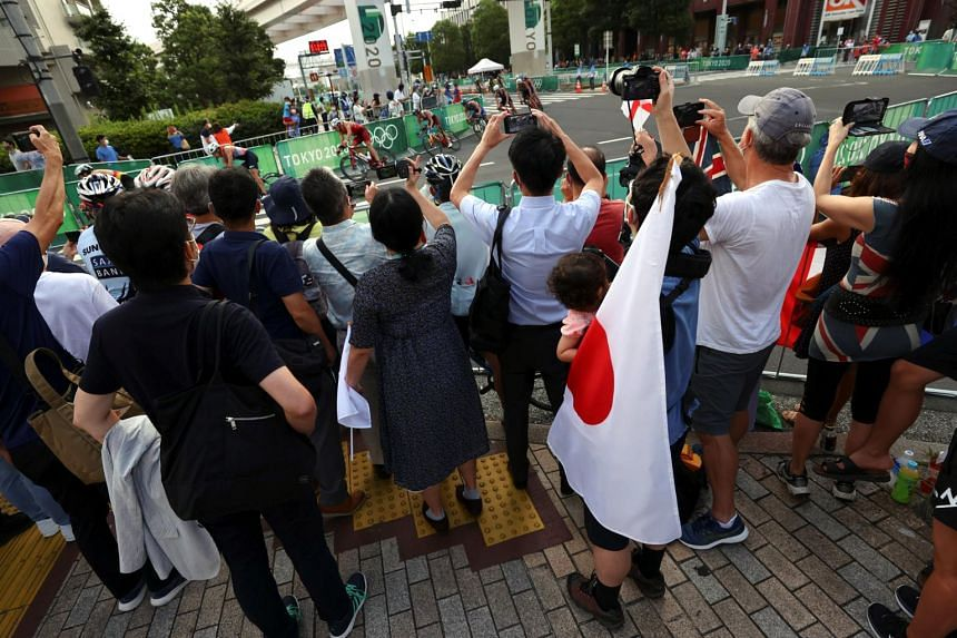 Fans and local residents try to catch a glimpse of the men's triathlon event.