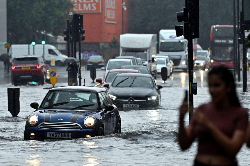 Cars drive through deep water on a flooded road in London, on July 25, 2021.