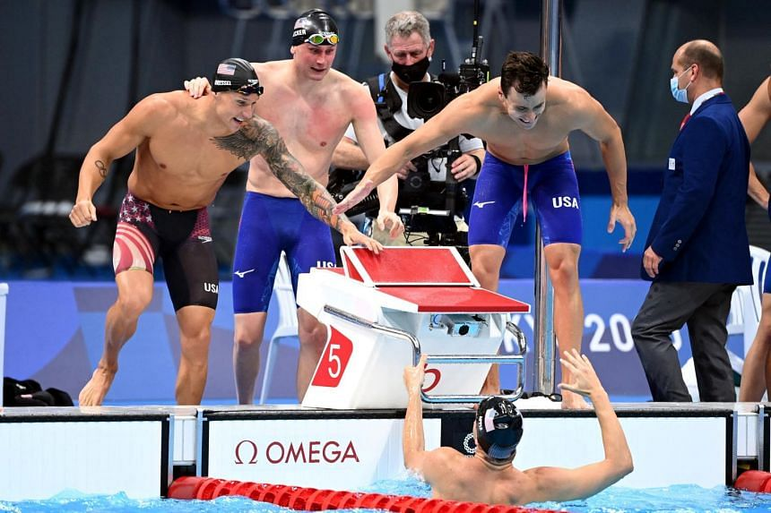 USA's Zach Apple (bottom) celebrating with teammates (from left) Caeleb Dressel, Blake Pieroni and Bowen Becker after winning the men's 4x100 freestyle relay in Tokyo on July 26, 2021.