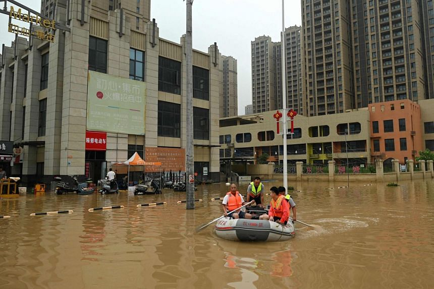 Rescue workers paddling through a flooded street following heavy rain in Zhengzhou in China's Henan province on July 23, 2021.