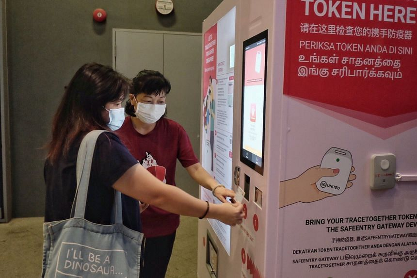 A Smart Nation Ambassador assisting the change of a TraceTogether token from the vending machine.