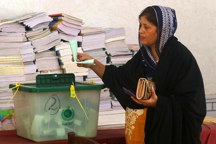 A Kashmiri woman casts her vote at a polling station in Karachi, on July 25, 2021.