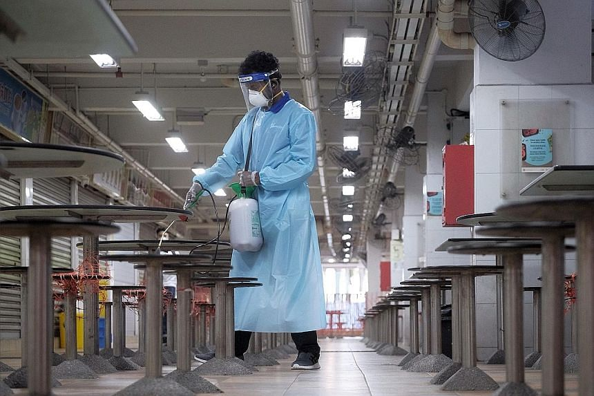 Hong Lim Market and Food Centre being disinfected on July 18. The cluster at Jurong Fishery Port was first discovered on July 16, with multiple infections detected at the port, as well as at Hong Lim Market and Food Centre.