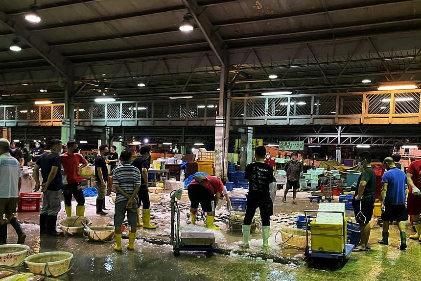 Workers at Jurong Fishery Port last month. The humid environment made it uncomfortable for them to wear their masks for a prolonged period.