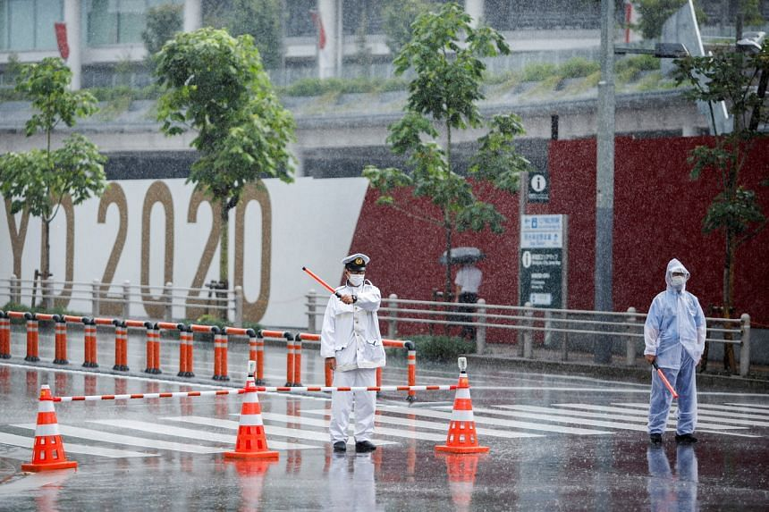 Traffic policemen control the traffic in front of the Olympic stadium in the rain caused by tropical storm Nepartak in Tokyo on July 27, 2021.