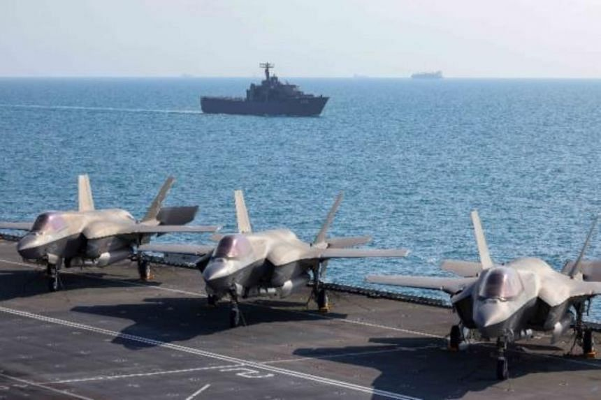 RSS Resolution, seen from the deck of HMS Queen Elizabeth. On the deck are US Marine Corps F-35B planes.