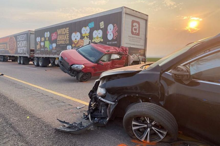 A red car lay balanced diagonally on two wheels against the back of a truck, its rear section severely crumpled.