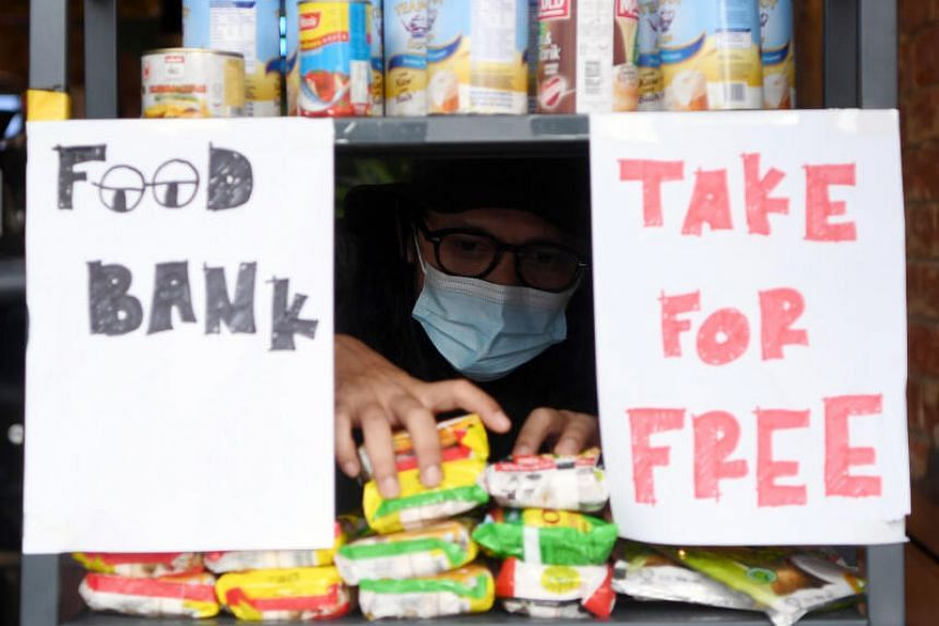 Ahmad Dainey Zainuddin arranges food items given out for free on the cafe premises to those adversely affected by the Covid-19 pandemic.