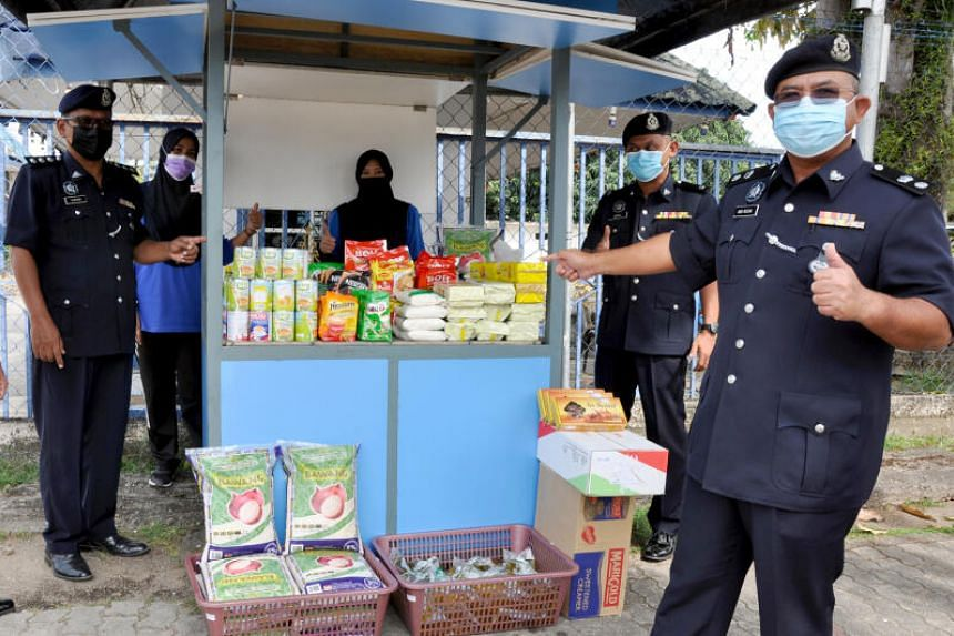 Besut District Police Chief Supt Abdul Rozak Muhammad (right) launches the food bank set up at the Besut police headquarters.