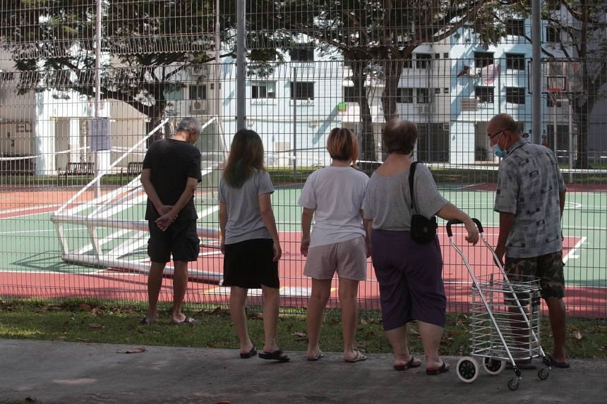People look at the fallen basketball structure near Block 18 Bedok South Road on July 27, 2021.