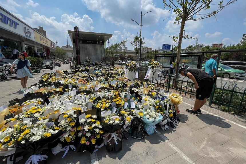 A man bows as people place flowers in front of a subway station in memory of flood victims in Zhengzhou, China's central Henan province on July 27, 2021.