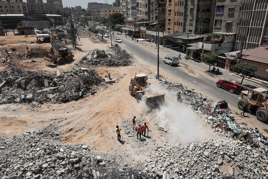 Palestinian workers clear the rubble of buildings, leveled by Israeli bombing during the conflict between Israel and Hamas in May this year.