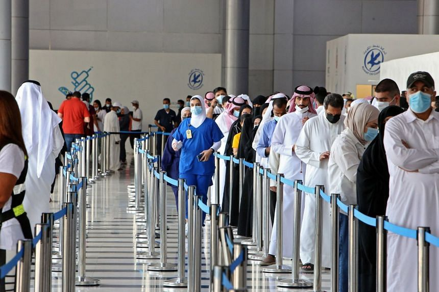 People queue to receive a dose of a Covid-19 coronavirus vaccine at a vaccination centre in Kuwait City, on July 20, 2021.