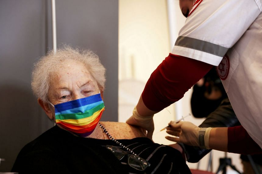 A January 2021 photo shows an elderly woman receiving a booster shot of her vaccination against coronavirus, in Netanya, Israel.