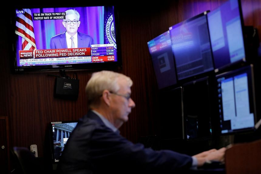 A screen displays a statement by Federal Reserve chairman Jerome Powell as a trader works on the floor at New York Stock Exchange.
