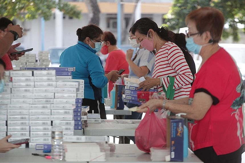 Residents collecting their free antigen rapid test self-test kits in Geylang Bahru on Monday. All households will progressively receive self-test kits.