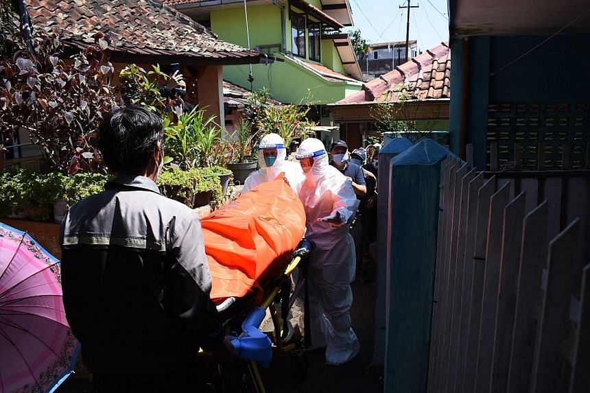 Health workers removing the body of a Covid-19 victim who died at home in Bandung, Indonesia, yesterday. Data from a citizen data platform shows 2,705 have died at home from Covid-19 in the last two months.