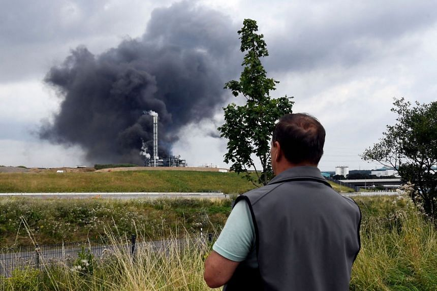 An onlooker watches as smoke rises from a landfill and waste incineration area at the Chempark industrial park, on July 27, 2021.