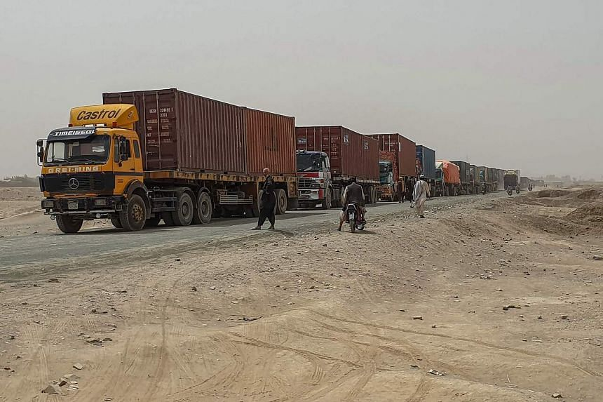 Drivers of Pakistani goods trucks wait along a street leading towards the Afghan border crossing point in Chaman, Pakistan, on July 28, 2021.