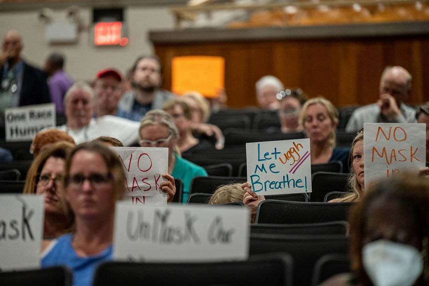 Demonstrators hold signs protesting against mask mandates during a school board meeting for the Jefferson County Public Schools district in Louisville, Kentucky.