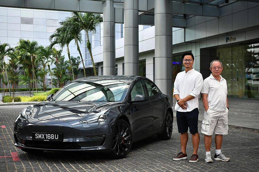 Lawyer Teng Po Yew and his father, retiree James Teng, with the new Tesla Model 3 at SPH News Centre yesterday. The younger Mr Teng was the first customer to collect his new Tesla car.