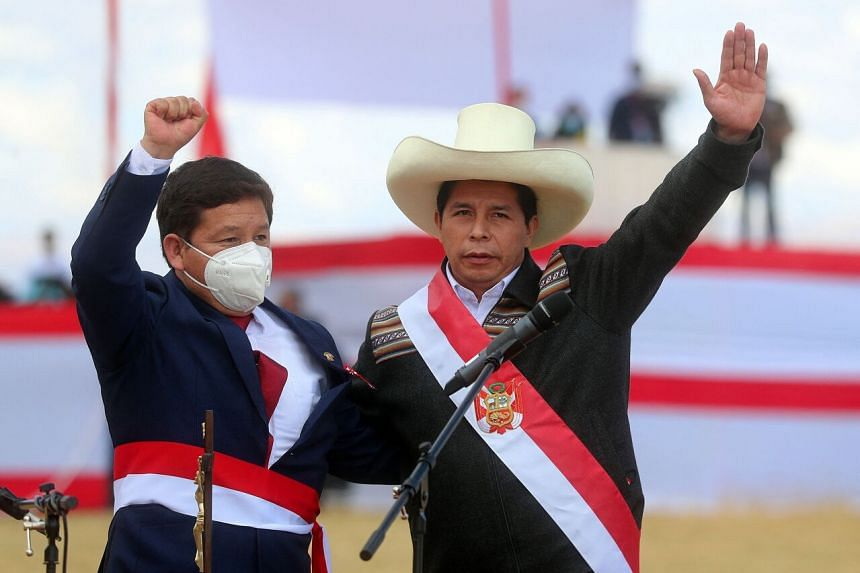 Peru's new Prime Minister Guido Bellido (right) and Peruvian President Pedro Castillo greeting their supporters at Pampa de la Quinua in Ayacucho, southern Peru, on July 29, 2021.